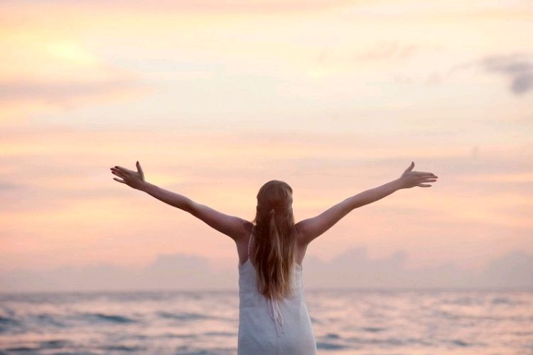A girl with her arms outstretched looking over the ocean at sunset. Staying motivated when you want to give up.